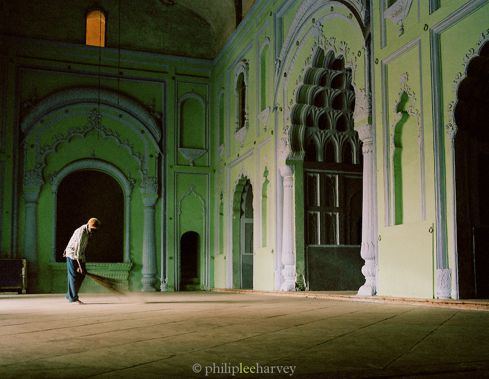 Caretaker sweeps the floor inside the Great Imambara, Lucknow, Uttar Pradesh, India