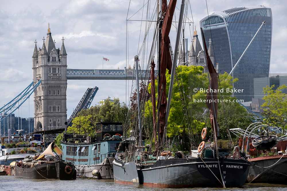 With Tower Bridge and the Walkie Talkie building in the distance, barges and lighters at Tower Bridge Moorings are grouped together on the river Thames, on 11th June 2021, in London, England. 'Xylonite' is one of seven Thames barges built between 1925 and 1930. Tower Bridge Moorings is the capital's only floating gardens - a sustainable way of living for a community of more than one hundred adults and children, and a shelter for wildlife on the river.