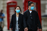 A couple walking hand-in-hand is seen wearing face protective surgical masks as they walk near Downing Street in central London on Sunday, Aug 8, 2021. Scientists are warning the public not to be complacent, saying high levels of infection in the community are likely to lead to another spike in cases this fall. (VX Photo/ Vudi Xhymshiti)