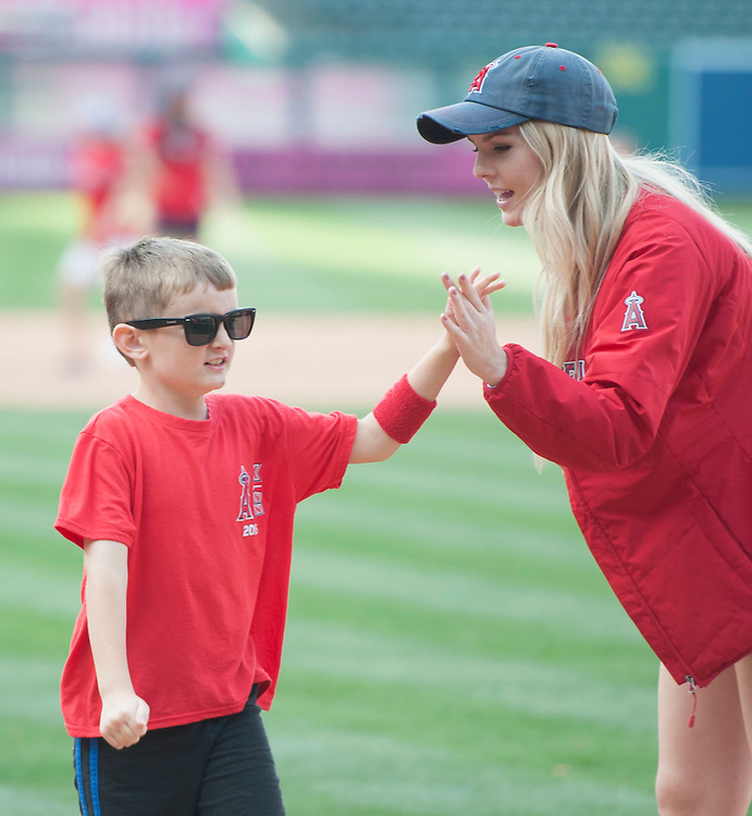 A member of the Angels Strike Force high fives a young fan as kids run the bases after the Angels game against the  Houston Astros Sunday at Angel Stadium.  <br /> <br /> ///ADDITIONAL INFO:   <br /> <br /> angels.0530.kjs  ---  Photo by KEVIN SULLIVAN / Orange County Register  -- 5/29/16<br /> <br /> The Los Angeles Angels take on the Houston Astros Sunday at Angel Stadium.