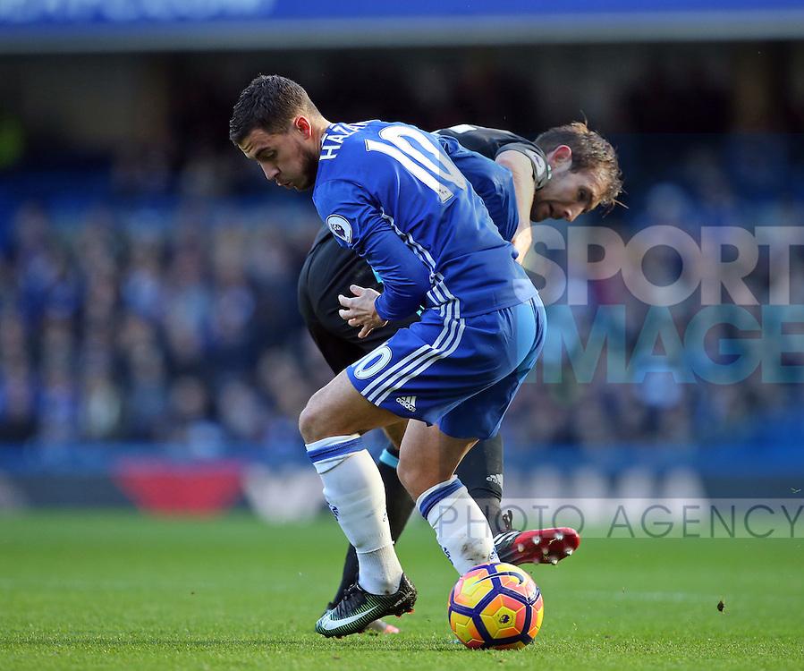 Chelsea's Eden Hazard tussles with WBA's Gareth McAuley during the Premier League match at Stamford Bridge Stadium, London. Picture date December 11th, 2016 Pic David Klein/Sportimage