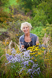 Carol Klein with asters, miscanthus, sedums and rudbeckias