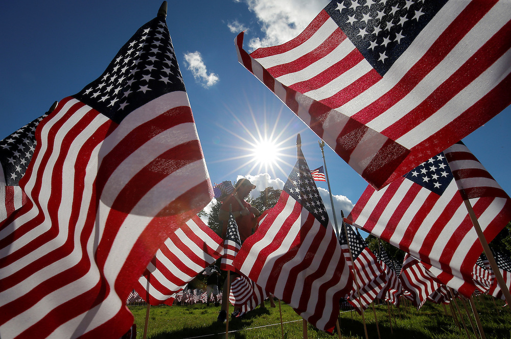 A man takes part in planting some of the 3,000 U.S. flags placed in memory of the lives lost in the September 11, 2001 attacks, at a park in Winnetka, Illinois, September 10, 2016.   REUTERS/Jim Young