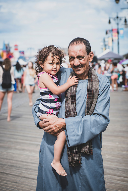 New York City, USA - July 10, 2016: Nabil, a Coptic Christian visiting from Cairo, holds his granddaughter Miriam during an outting on the Coney Island boardwalk in New York,