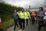 Anti-fracking  activists and protesters outside the gates of Quadrillas fracking site June 31st, Lancashire, United Kingdom. An activist is arrested for jumping on a truck bringing equipment after he handed himself over. The struggle against fracking in Lancashire has been going on for years. The fracking company Quadrilla is finally ready to bring in a drill tower to start drilling and anti-frackinhg activists are waiting in front of the gates to block the equipment getting in. Fracking is a destructive and potential dangerous and highly contentious method of extracting gas and this site will be the first of many in the United Kingdom reaching miles out under ground.