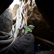 April 28, 2012 - Tabania, Nuba Mountains, South Kordofan, Sudan: A Nuba woman takes cover, from possible bombardments by Sudan's Army Forces airplane, in some caves near Buram village...Since the 6th of June 2011, the Sudan's Army Forces (SAF) initiated, under direct orders from President Bashir, an attack campaign against civil areas throughout the South Kordofan's province. Hundreds have been killed and many more injured...Local residents, of Nuba origin, have since lived in fear and the majority moved from their homes to caves in the nearby mountains. Others chose to find refuge in South Sudan, driven by the lack of food cause by the agriculture production halt due to the constant bombardments of rural areas. (Paulo Nunes dos Santos/Polaris)