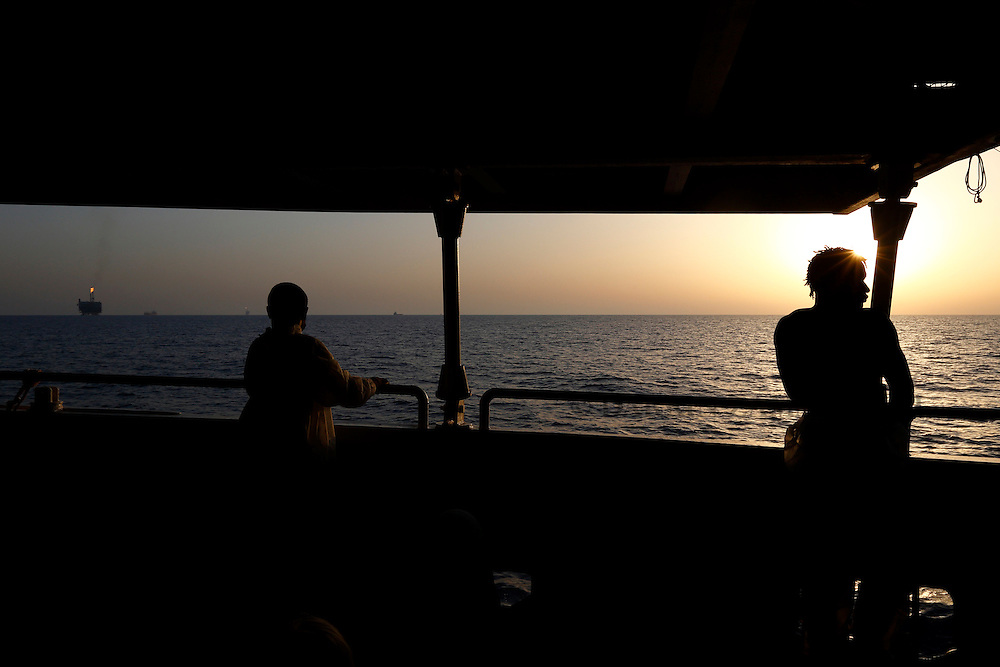 Rescued migrants on the deck of the Migrant Offshore Aid Station (MOAS) ship MV Phoenix look out at the Bouri Oil Field between Libya and the Italian island of Lampedusa, at sunset, August 3, 2015.  118 migrants were rescued by the Phoenix from a rubber dinghy some 20 miles (32 kilometres) off the coast of Libya on Monday morning. The Phoenix, manned by personnel from international non-governmental organisations Medecins san Frontiere (MSF) and MOAS, is the first privately funded vessel to operate in the Mediterranean.<br /> REUTERS/Darrin Zammit Lupi <br /> MALTA OUT. NO COMMERCIAL OR EDITORIAL SALES IN MALTA
