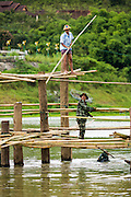 16 SEPTEMBER 2014 - SANGKHLA BURI, KANCHANABURI, THAILAND: A member of the Mon community and a Thai soldier work on the bamboo scaffolding for the repair of the Mon Bridge. The 2800 foot long (850 meters) Saphan Mon (Mon Bridge) spans the Song Kalia River. It is reportedly second longest wooden bridge in the world. The bridge was severely damaged during heavy rainfall in July 2013 when its 230 foot middle section  (70 meters) collapsed during flooding. Officially known as Uttamanusorn Bridge, the bridge has been used by people in Sangkhla Buri (also known as Sangkhlaburi) for 20 years. The bridge was was conceived by Luang Pho Uttama, the late abbot of of Wat Wang Wiwekaram, and was built by hand by Mon refugees from Myanmar (then Burma). The wooden bridge is one of the leading tourist attractions in Kanchanaburi province. The loss of the bridge has hurt the economy of the Mon community opposite Sangkhla Buri. The repair has taken far longer than expected. Thai Prime Minister General Prayuth Chan-ocha ordered an engineer unit of the Royal Thai Army to help the local Mon population repair the bridge. Local people said they hope the bridge is repaired by the end November, which is when the tourist season starts.    PHOTO BY JACK KURTZ