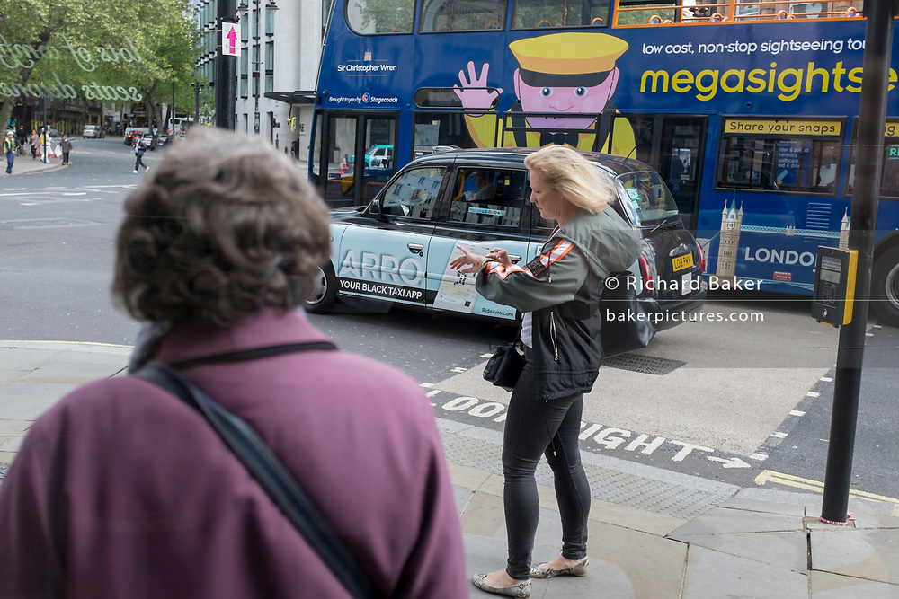 As a Megasightseeing tour bus drives past in Aldwych WC2 at the north end of Waterloo Bridge, a woman checks her watch, on 2nd May 2019, in London, England.