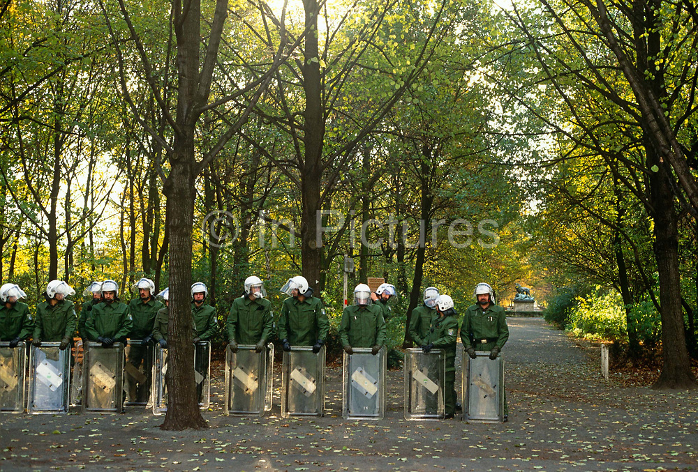 Awaiting the call-up from superior officers, a phalanx of German riot police stand in their ranks, with shields resting on the ground of a central Berlin park. Their orders will be to keep control of protesters in the former eastern sector of the German city, in the months after the fall of the Wall and the communist state, the GDR (German Democratic Republic) or DDR. Because Germany is now one country (though reunification itself has yet to happen), West German officers of the Bundespolizei (BPOL) which is the uniformed federal police force of Germany, wait patiently for orders from their western masters. The Bundespolizei consists of around 40,000 personnel, from border control, aviation wings, civil servants, immigration services and riot control (Beweissicherungs and Festnahmeeinheit).
