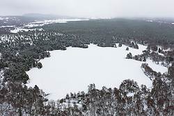 Aerial view of frozen Loch Vaa with small boathouse, Aviemore, Scotland, UK