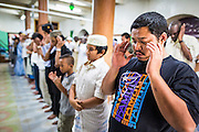 "08 AUGUST 2013 - BANGKOK, THAILAND: Men pray during Eid al-Fitr services at Haroon Mosque in Bangkok. Eid al-Fitr is the ""festival of breaking of the fast,"" it's also called the Lesser Eid. It's an important religious holiday celebrated by Muslims worldwide that marks the end of Ramadan, the Islamic holy month of fasting. The religious Eid is a single day and Muslims are not permitted to fast that day. The holiday celebrates the conclusion of the 29 or 30 days of dawn-to-sunset fasting during the entire month of Ramadan. This is a day when Muslims around the world show a common goal of unity. The date for the start of any lunar Hijri month varies based on the observation of new moon by local religious authorities, so the exact day of celebration varies by locality.      PHOTO BY JACK KURTZ"