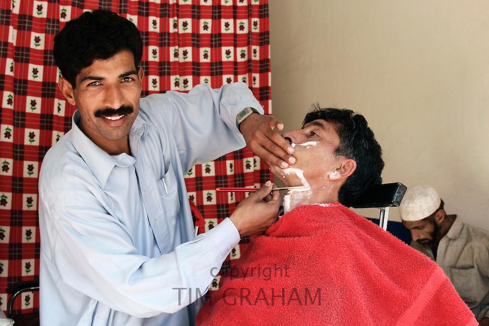 Man visits barber shop in village of Pattika, Pakistan