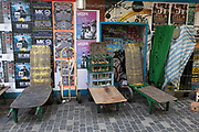 Old fruit and vegetable market stall carts stand in front of a wall covered in music posters on Berwick Street in Soho, London, United Kingdom.