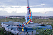 Multi-coloured ribbons blurs from the mast of a small covered yacht that sits on beach shingle, on a low-tide evening sunset, on 27th July 2021, in Whitstable, Kent, England.