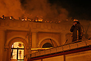 Moscow, Russia, 14.03/2004..Two firemen died fighting a huge blaze which engulfed the Manezh exhibition hall, one of Russia's most historic buildings, located only yards from the Kremlin. A firemen smokes a cigarette while the Manezh burns behind.