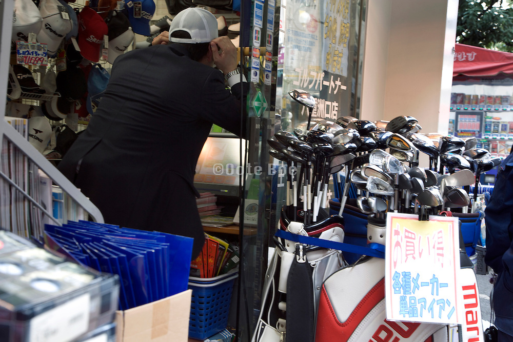 businessman fitting cap in sports store with golf sticks on sale
