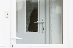 © Licensed to London News Pictures . 17/01/2015 . Stockport , UK . Smashed front door glass at 28 Meadway Road , Cheadle Hulme , Stockport this afternoon (Saturday 17th January 2015 ) after a man and a woman in their 40s were found dead inside last night (16th January 2015) . A neighbour described hearing a commotion and seeing a man smash the front door with a hammer to gain entry . Photo credit : Joel Goodman/LNP