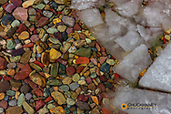 Ice and colorful shore rocks along wintry Lake McDonald in Glacier National Park, Montana, USA