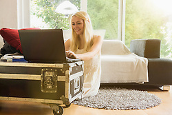 Beautiful young woman using laptop in the living room and smiling, Munich, Bavaria, Germany