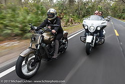Riding through Tamoka State Park, Klock Werks Karlee Kobb on her custom Indian Scout with Brian Klock on his Limited Edition Jack Daniels Indian Chieftain that Brian designed for Indian during Daytona Beach Bike Week. FL. USA. Monday March 13, 2017. Photography ©2017 Michael Lichter.