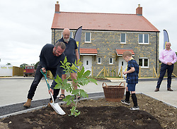 David Beckham (left) and Michael Eavis (second left) plant a tree outside a completed house in a housing development in Pilton village in Somerset.