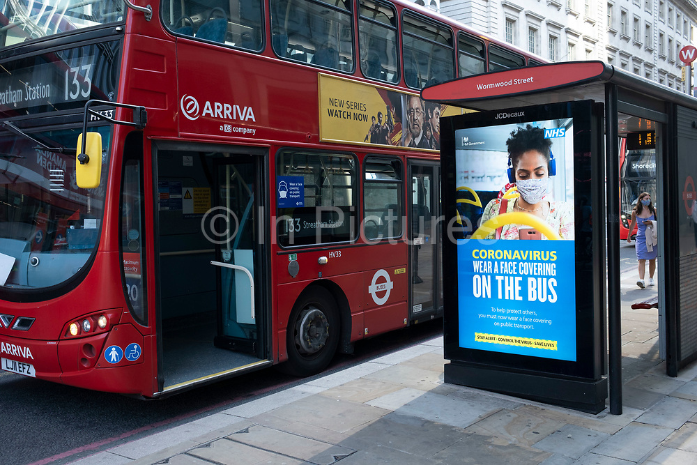 Public transport HM Government and NHS advertising boards instruct people to wear a face covering or face mask on the tube or buses on the day that it was announced that the Coronavirus lockdown measures are set to ease even further and the quiet city starts coming to an end, on 23rd June 2020 in London, England, United Kingdom. As of today the government has relaxed its lockdown rules, and is allowing some non-essential shops to open with individual shops setting up social distancing queueing systems.