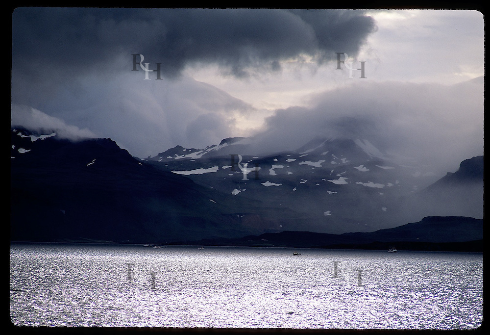 Clouds shroud mountains as fishing boats go to sea on a summer day along Snaefell Peninsula. Iceland