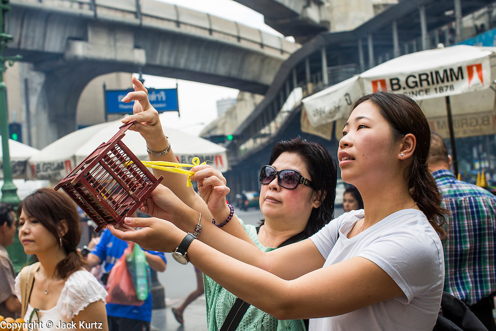 27 SEPTEMBER 2012 - BANGKOK, THAILAND:  Women pray after they released birds to make good kharma at the Erawan Shrine in Bangkok. The Erawan Shrine is a Hindu shrine in Bangkok, Thailand, that houses a statue of Phra Phrom, the Thai representation of the Hindu creation god Brahma. A popular tourist attraction, it often features performances by resident Thai dance troupes, who are hired by worshippers in return for seeing their prayers at the shrine answered. The Erawan Shrine was built in 1956 as part of the government-owned Erawan Hotel to eliminate the bad karma believed caused by laying the foundations on the wrong date. The hotel's construction was delayed by a series of mishaps, including cost overruns, injuries to laborers, and the loss of a shipload of Italian marble intended for the building. Furthermore, the Ratchaprasong Intersection had once been used to put criminals on public display. An astrologer advised building the shrine to counter the negative influences. The Brahma statue was designed and built by the Department of Fine Arts and enshrined on 9 November 1956. The hotel's construction thereafter proceeded without further incident. In 1987, the hotel was demolished and the site used for the Grand Hyatt Erawan Hotel.     PHOTO BY JACK KURTZ