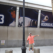 A fan arriving to the ball game has his picture taken in front of the Alex Rodriguez banner in front of Yankee Stadium before the New York Yankees V Detroit Tigers Major League Baseball regular season baseball game at Yankee Stadium, The Bronx, New York. 11th August 2013. Photo Tim Clayton