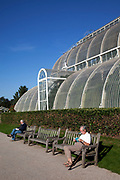 A regular comes to sit in the sun and read outside the Palm House at Kew Gardens in the autumn, London. The Royal Botanic Gardens, Kew, usually referred to simply as Kew Gardens, are 121 hectares of gardens  and botanical glasshouses between Richmond and Kew in southwest London, England. It is an internationally important botanical research and education institution with 700 staff, receiving around 2 million visitors per year.