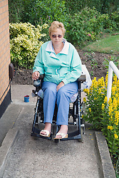 Woman wheelchair user entering her home using a concrete ramp,