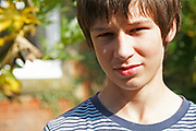 Portrait of teenage boy looking straight at camera informal clothes brown hair