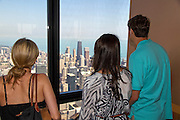 Aerial view of Chicago IL as seen from the Willis tower (formerly Sears tower) observation deck. People overlooking the John Hancock building.