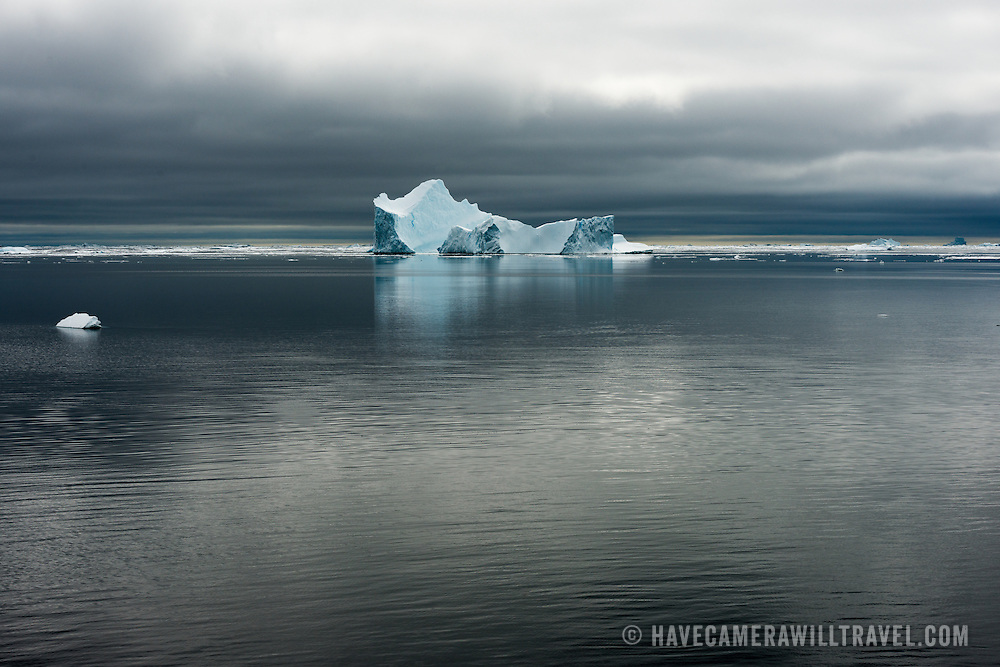 An Antarctic Iceberg's subtle coloring stands out against the calm waters and gray skies near Galindez Island in Antarctica.