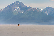 A kite surfer rides the bore tide past snow capped mountains on Turnagain Arm at Windy Point outside Anchorage, Alaska.