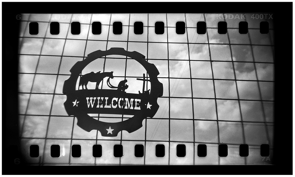 A welcome sign is seen on a gate in Crawford, Texas, in this photo taken November 10, 2008. U.S. President George W. Bush moved to the small Texas town, population 705, in 1999 during his run for the presidency in 2000. The effect of the image was achieved by shooting 35mm black and white film in a medium format camera thereby exposing the entire negative including the sprocket holes of the film. REUTERS/Jim Young
