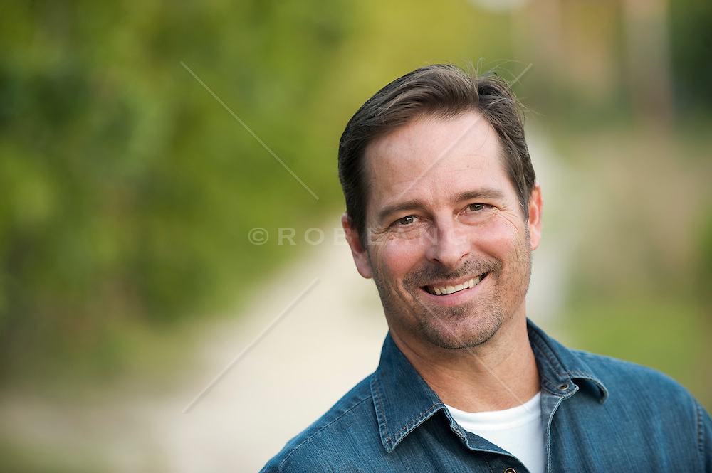 Portrait of a man smiling wearing a denim button down shirt