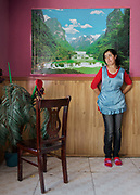 Waitress waiting for customers in a restaurant in Khorog in front of a Made in China poster depicting Chinese landscapes.<br /> Tajikistan, a mountainous landlocked country in Central Asia. Afghanistan borders it to the south, Uzbekistan to the west, Kyrgyzstan to the north, and People's Republic of China to the east. Tajikistan also lies adjacent to Pakistan separated by the narrow Wakhan Corridor.<br /> Tajikistan became a republic of the Soviet Union in the 20th century, known as the Tajik Soviet Socialist Republic.<br /> It was the first of the Central Asian republic to gain independence in December 1991.