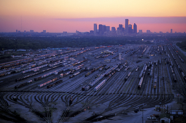Trains in a rail yard with downtown Houston skyline on the horizon at sunset.