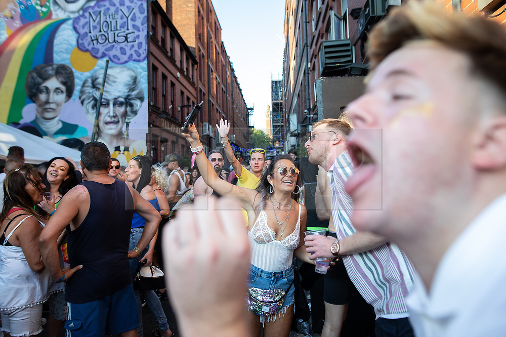 © Licensed to London News Pictures . 25/08/2019. Manchester, UK. People dance , take selfies and gesture in the street outside the Molly House pub . Revellers in Manchester's Gay Village during the city's annual Gay Pride festival , which celebrates LGBTQ+ life and is the largest of its type in Europe . Photo credit: Joel Goodman/LNP