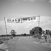 A vaccinator carrying the vaccine on a bicycle passes under a polio gate sponsored by PRI members. Raniganj block, Araria district, Bihar
