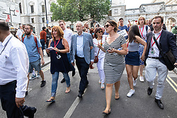 © Licensed to London News Pictures . 13/07/2018. London, UK. JEREMY CORBYN and his wife LAURA ALVAREZ are lead from Trafalgar Square along The Mall , Horse Guards Parade and across Whitehall by dozens of police after speaking to thousands of demonstrators in Trafalgar Square at a rally in protest against US President Donald Trump's UK visit . Photo credit: Joel Goodman/LNP