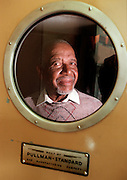 "Portrait of Garrard ""Babe"" Smock, 78, a former Pullman car porter, behind a Pullman train car door."