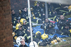 June 14, 2017 - London,UK -  A large group of firefighters rest at the scene of a huge fire at Grenfell tower block in White City, London. The blaze engulfed the 27-story building with 200 firefighters attending the scene. There were at least six people who died in the blaze. (Credit Image: © Guilhem Baker/London News Pictures via ZUMA Wire)