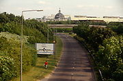 A lone woman pedestrian has to walk along a grass verge to enter the outer limits of Milton Keynes.