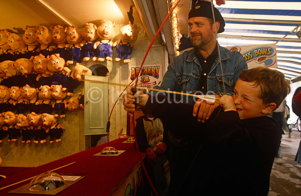 A father helps his young son to fire a bow and arrow at the fairground on Brighton Pier. Taking careful aim with one eye closed and the other open, the young lad points the pretend arrow to an unseen target with the promise of stuffed pigs lining the right-hand wall of this kiosk. The dad helps by holding the centre of the bow for the boy, steadying the aim.