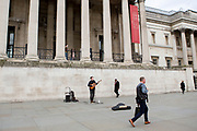 UNITED KINGDOM, London: 13 March 2020 <br /> A busker at Trafalgar Square plays to no one as London streets and landmarks, which are usually packed with visitors and Londoners alike, are deserted as the pandemic of the coronavirus takes effect in the capital city. The Coronavirus pandemic has now reached the 'delay' phase, which was announced by British Prime Minister Boris Johnson yesterday.