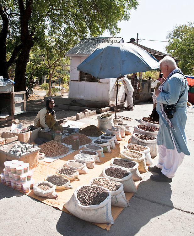 Spice market: customer and seller in discussion over neat rows of bagged spices, beans, grains, nuts, and other foods.