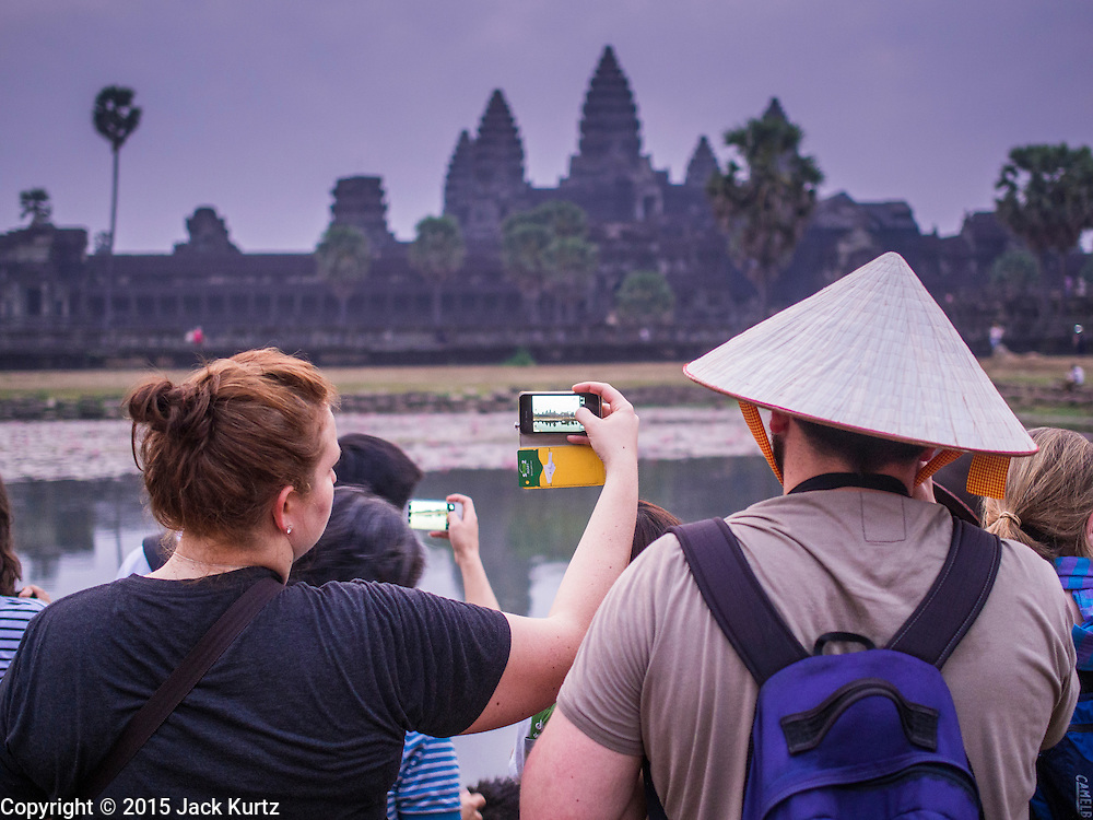 """14 MARCH 2105 - SIEM REAP, SIEM REAP, CAMBODIA: Tourists, one with a Vietnamese style conical hat, photograph Angkor Wat with their smart phone at sunrise. The area known as """"Angkor Wat"""" is a sprawling collection of archeological ruins and temples. The area was developed by ancient Khmer (Cambodian) Kings starting as early as 1150 CE and renovated and expanded around 1180CE by Jayavarman VII. Angkor Wat is now considered the seventh wonder of the world and is Cambodia's most important tourist attraction.   PHOTO BY JACK KURTZ"""